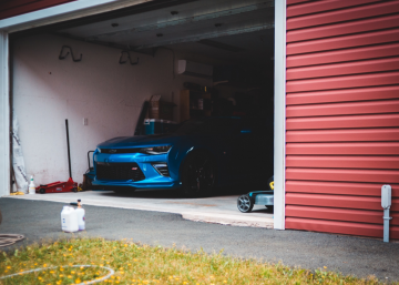 Car in a garage with red garage door visible